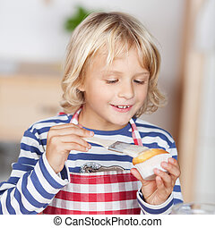 Little girl glazing a cupcake - Cute little blond girl...
