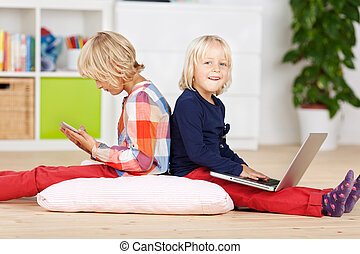 Two small young girls using a laptop and tablet - Two small...