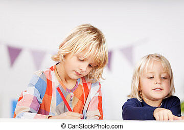 Two young sisters drawing pictures together - Two small...