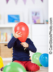 Playful girl hiding behind a red balloon - Playful little...