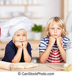 Siblings Looking Away While Leaning On Kitchen Counter