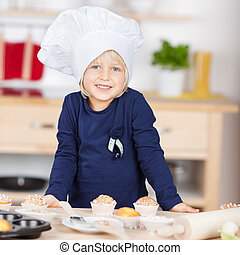 Cute little blond girl in a chefs toque or hat leaning on a...