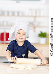 Little Girl Using Rolling Pin On Dough At Kitchen Counter -...