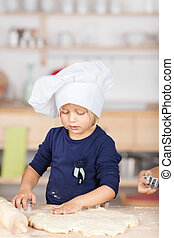 Girl Using Cutter On Dough - Little girl using cutter on...