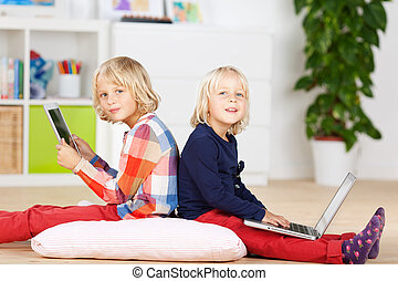 Girls With Laptop And Digital Tablet Sitting On Pillow -...
