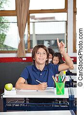 Happy Schoolboy Raising Hand In Classroom