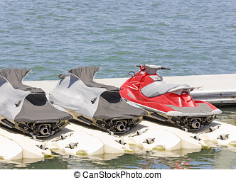 Personal water craft, jet skis at the dock - Bright red jet...