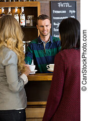 Young Bartender Serving Coffee To Female Friends At...