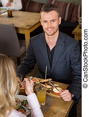 Businessman Having Food With Female Colleague In Cafe