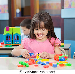 Girl Playing With Colorful Blocks In Classroom - Happy...