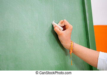 Girls Hand Writing On Green Chalkboard In Kindergarten -...