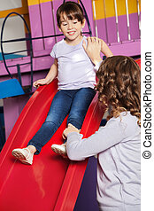 Teacher Assisting Girl While Playing On Slide - Young...