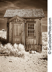 Small old building in sepia tone in a high desert ghost...