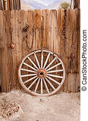 Wagon wheel and fence - Broken wagon wheel resting against a...