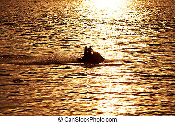 Silhouette of people on jet-ski against the sunset at sea