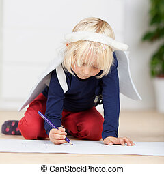 Young girl in angel wings drawing on the floor - Cute young...