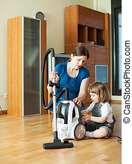Woman teaches  girl to use the vacuum cleaner