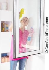woman washing the window glass - Young woman washing the...