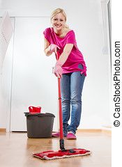Young Woman Cleaning Home - Young woman cleaning and mopping...