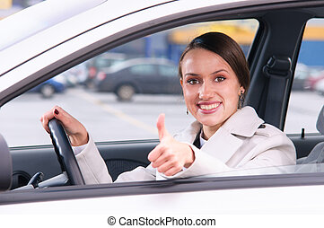 happy woman driver - happy woman is showing a thumb from a...