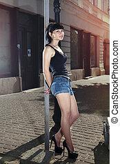 beautiful hitchhiker - beautiful woman stands near wall of...