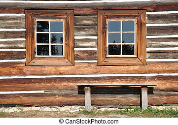 Wooden cottage facade with windows and bench