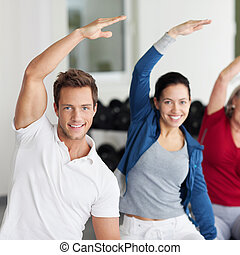Group Doing Stretching Exercise In Gym - Portrait of happy...