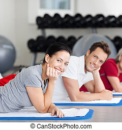 Woman With Group Lying On Mat At Gym - Portrait of smiling...