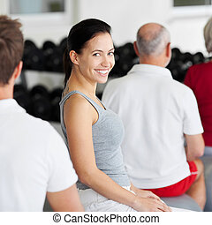 Woman Smiling With Group Sitting On Fitness Ball