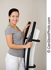 Woman With Exercise Machine In Gym