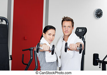 Healthy couple holding dumbbells in the gym with towel...