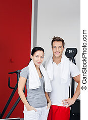 Couple in gym - Smiling couple training in the gym with...