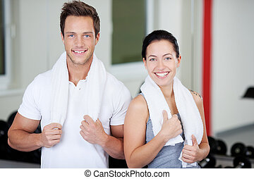 Couple With Towels Standing Together In Gym - Portrait of...