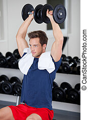 Muscular Man Exercising With Weight - Young muscular man...