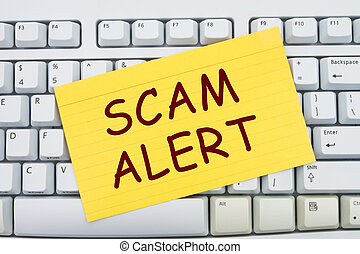 Scam Alert - Computer keyboard keys with index card with...