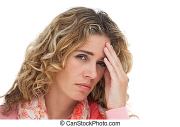 Blonde woman suffering with headache and holding her head on...