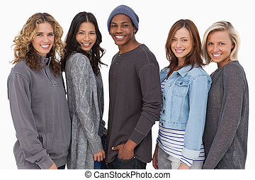 Fashionable young people in a row smiling on white...