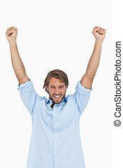 Happy man celebrating success with arms up on white...