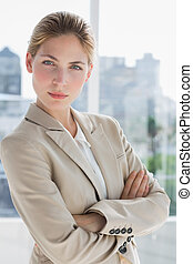 Businesswoman standing with arms crossed in a bright office