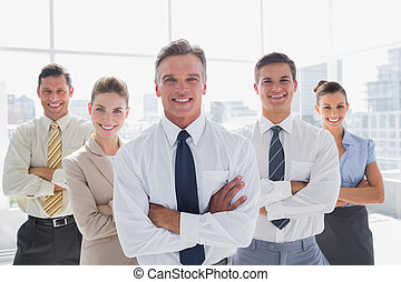 Smiling business people with arms crossed in their office -...