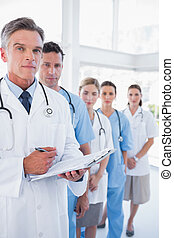Serious doctor holding clipboard and standing in front of his medical team in row
