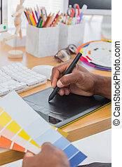 Interior designer with graphics tablet and colour chart in a...