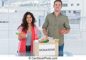 Smiling volunteers taking out food from donations box for a...