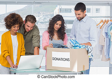 Volunteers using a laptop and taking clothes from charity box
