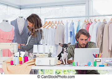 Fashion designers at work with a puppy on the desk in the...
