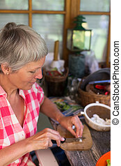 Senior woman cutting food - Senior woman with white hairs...