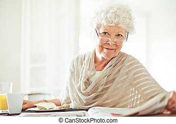 Old Lady with the Morning Newspaper - Happy senior woman...