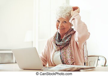 Cheerful Grandmother at Home with Laptop - Cheerful...