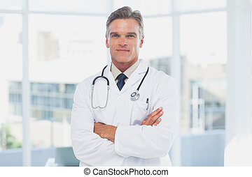 Grey haired doctor with arms crossed