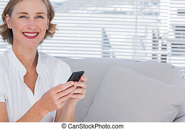 Smiling businesswoman using her mobile phone in bright...